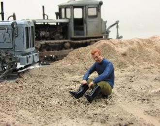 Мужчина в синей рубашке, сидящий на земле