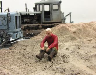 Мужчина в красной рубашке, сидящий на земле