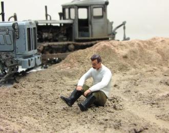 Мужчина в белой рубашке, сидящий на земле